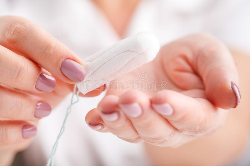 Woman`s hand holding a clean cotton tampon stock images