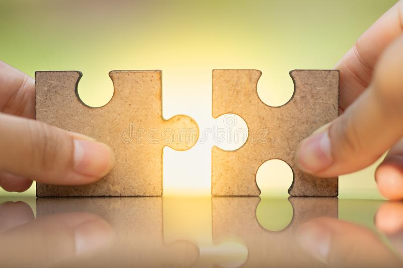 Woman`s hand holding and connecting jigsaw puzzles. royalty free stock photo