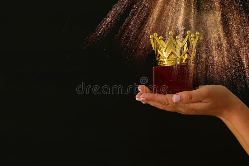 Woman& x27;s hand holding a crown trophy for show victory or winning first place over black background with glitter overlay. royalty free stock image