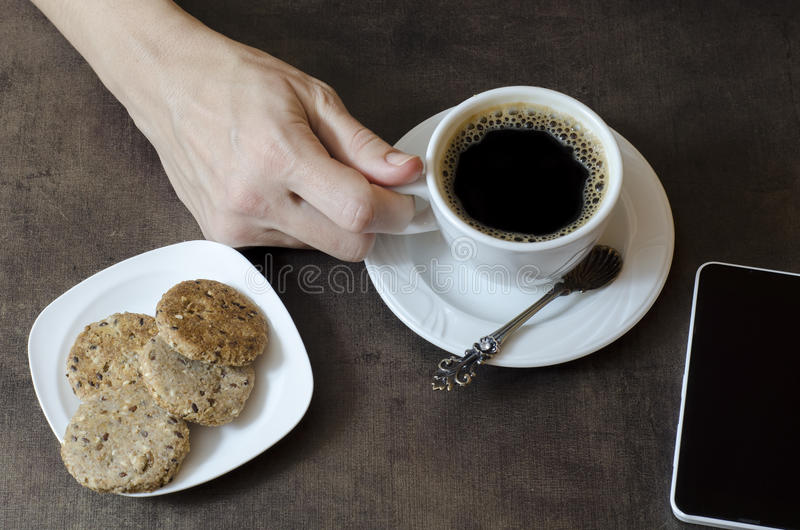 Woman's hand holding a cup of coffee stock photo