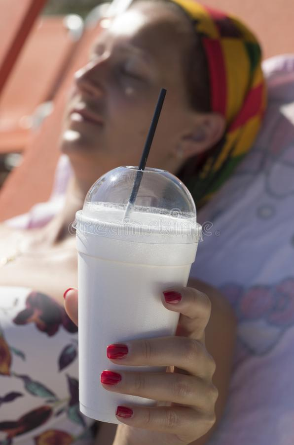 Woman`s hand holding a cup of Greek frappe with drinking straw royalty free stock photography
