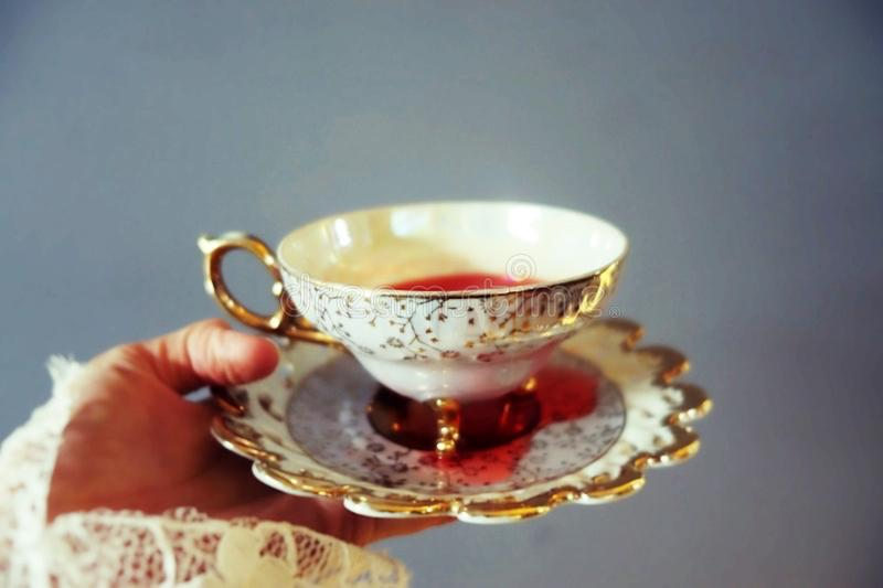 Woman`s hand holding delicate tea cup and saucier full of red liquid stock photos