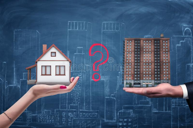 Woman`s hand holding a detached house and a man`s hand holding a brick block of flats with a question mark between them. stock photo