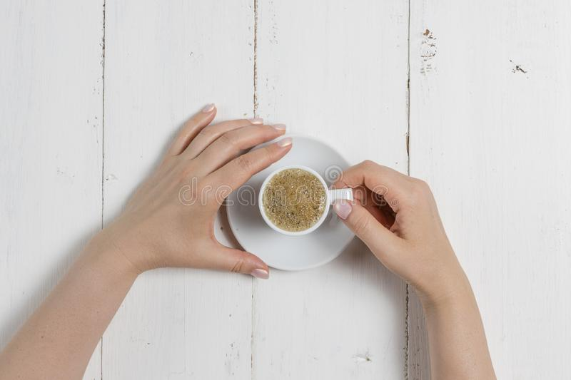 A woman`s hand holding an espresso cup royalty free stock photos