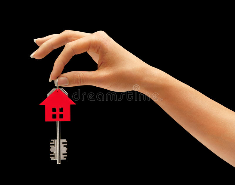 Woman's hand holding house key with keychain in the form of home stock image