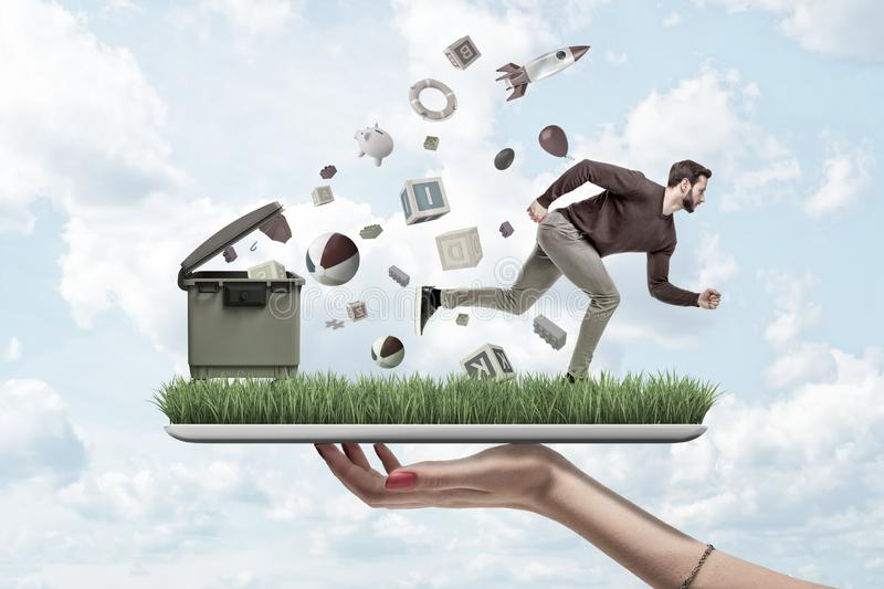 Woman`s hand holding ipad with green grass growing on screen and man running from things flying out of trash can that is stock image