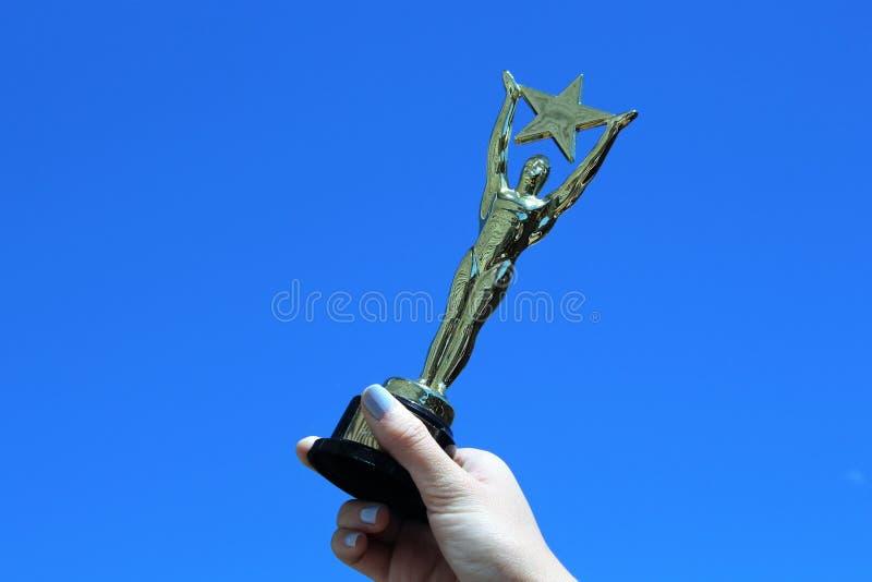 Woman`s Hand Holding Oscar-like Star Trophy Against Blue Sky. A woman`s hand holds an Oscar-like star trophy against a blue sky, signifying success, horizontal stock image