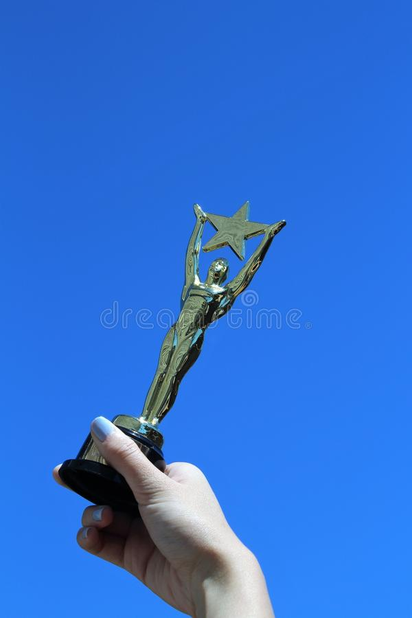 Woman`s Hand Holding Oscar-like Star Trophy Against Blue Sky. A woman`s hand holds an Oscar-like star trophy against a blue sky, signifying success, vertical royalty free stock photography