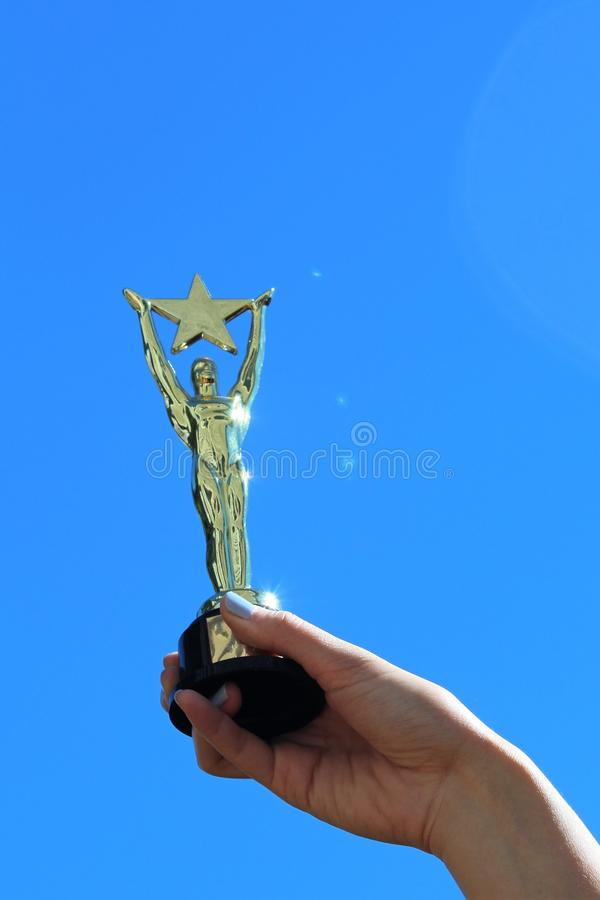 Woman`s Hand Holding Oscar-like Star Trophy Against Blue Sky. A woman`s hand holds a sparkling Oscar-like star trophy against a blue sky, signifying success royalty free stock image