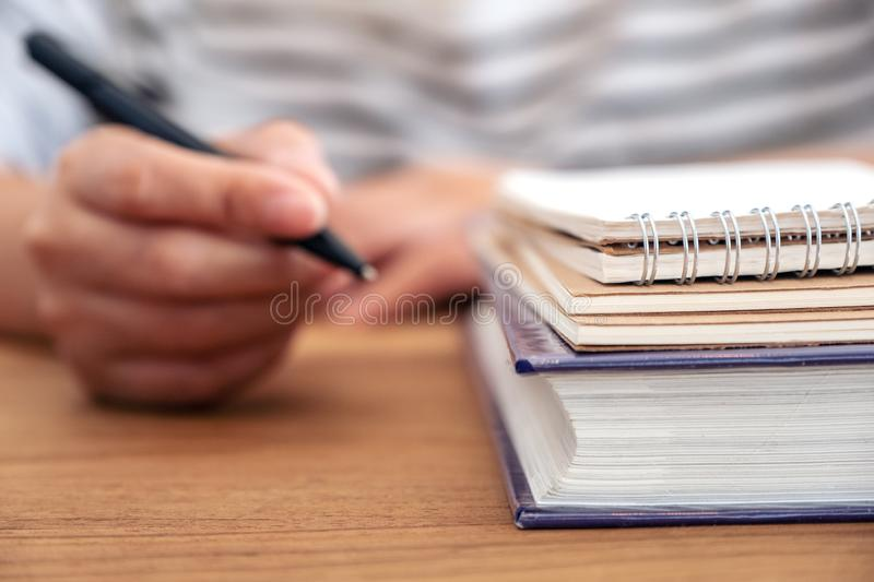 A woman`s hand holding a pen to write on a notebook and books on wooden table royalty free stock photo