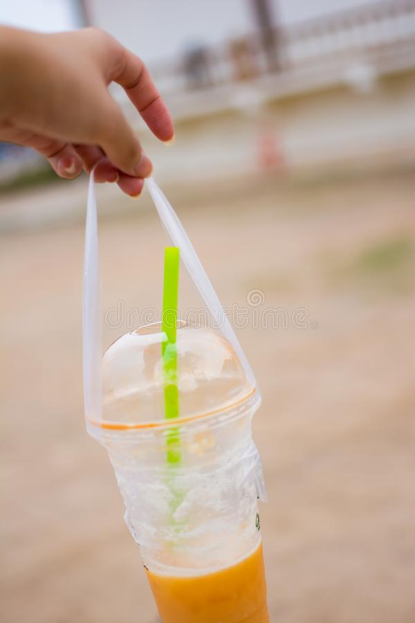 The woman`s hand is holding a plastic cup of Thai tea, picture in blurred background royalty free stock photo