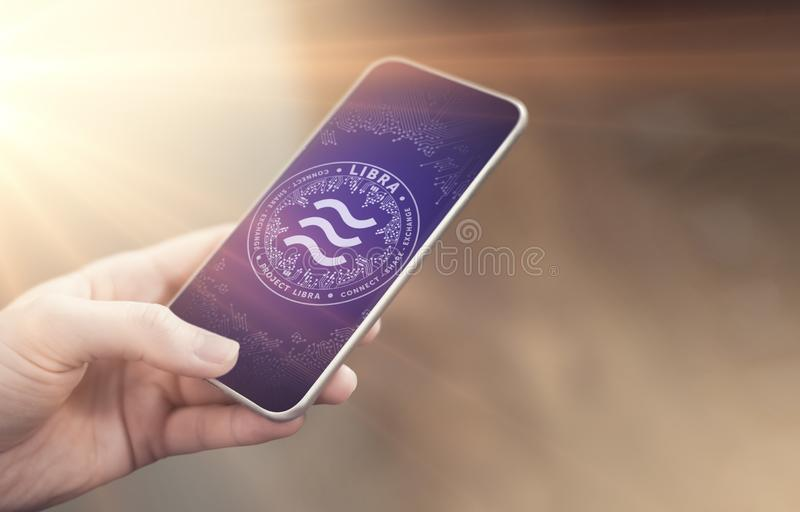 Woman`s hand holding smartphone with Libra symbol on screen. On-line payments, e-business and e-trade concept. New virtual money stock photo