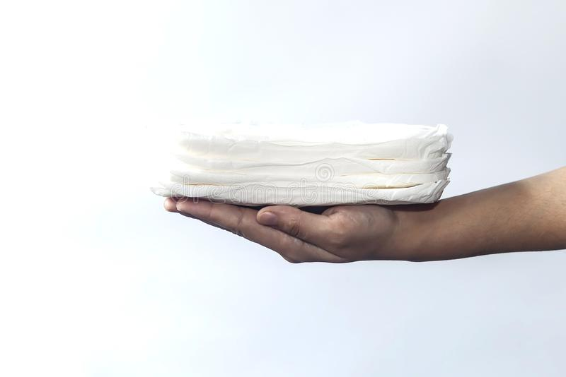Woman`s hand holding a stack of sanitary napkins against white background. Period days concept showing feminine menstrual cycle. Woman`s hand holding a stack of royalty free stock images