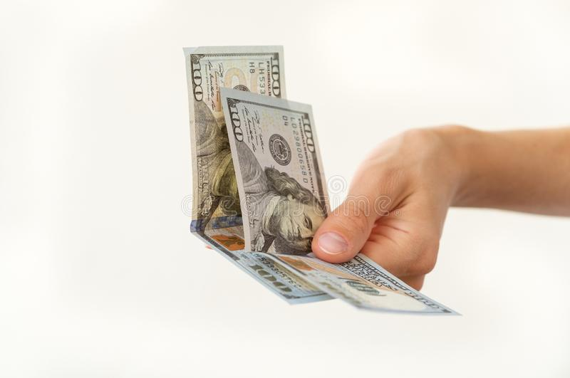 Woman`s hand is holding two hundreds of dollars stock photo