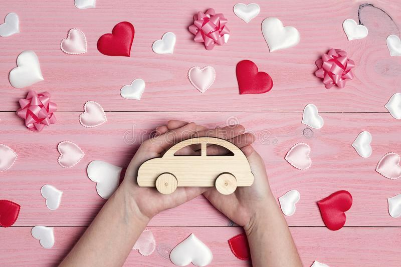 Woman`s hand holding a wooden toy car on love pink background royalty free stock photo