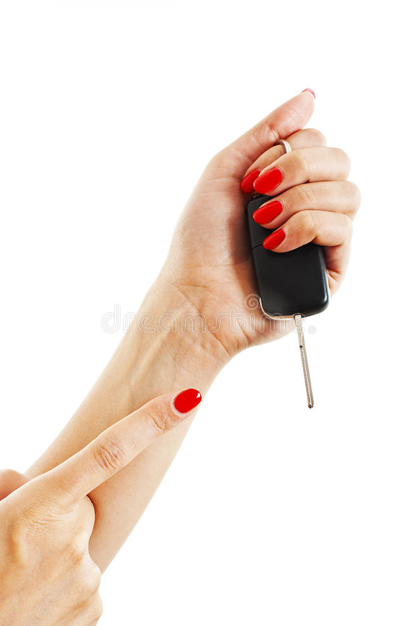 A woman's hand holds car keys. Isolated on white background stock photography