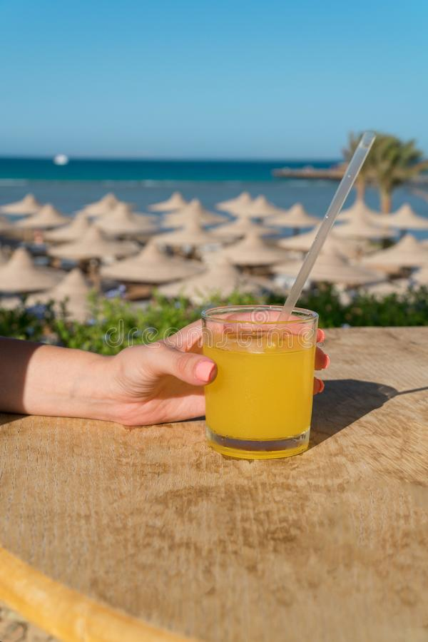 A woman`s hand holds a straw. Glass of fresh orange juice against the sea royalty free stock photos
