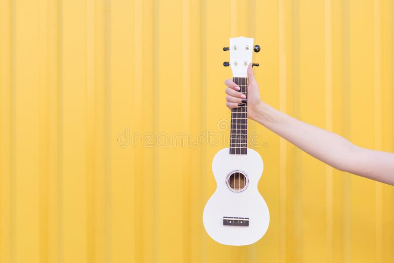 Woman`s hand holds ukulele on a yellow background. Musical concept. Music as a hobby. A woman`s hand holds ukulele on a yellow background. Musical concept. Music stock photography