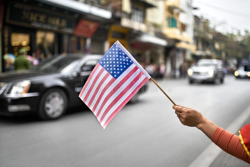 Citizen with flag welcomes diplomatic escort car passage. Woman`s hand holds the USA flag on the blurred background of the moving cars of the american diplomatic royalty free stock photography