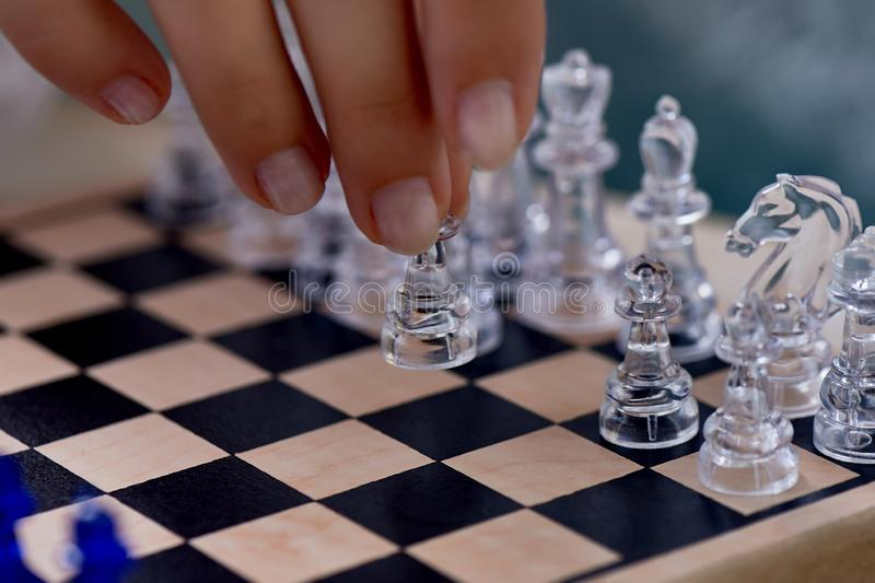 A woman`s hand moves the pieces on the chessboard. Finding solutions, brain activity.The development of the mind. A woman`s hand moves the pieces on the royalty free stock photos