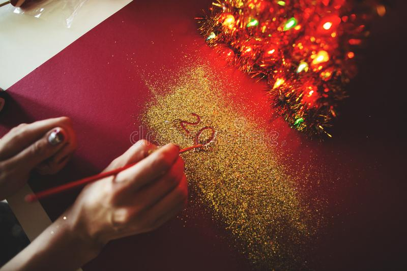 The woman`s hand paint the figure of 2020 in the claret background with sparkles. New Year`s concept.  stock photo