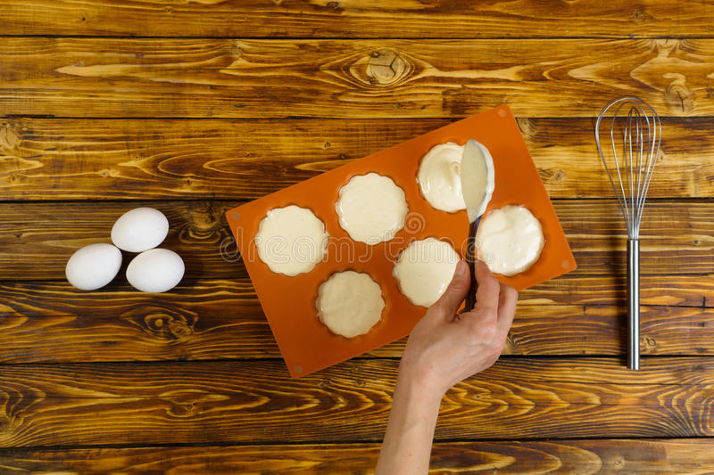 Woman`s hand puts dough in silicon form for muffins royalty free stock photo