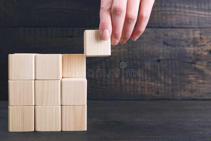 Woman`s hand putting the final piece of wooden cube into place - achievement concept. Finish the project concept. In a natural light royalty free stock image
