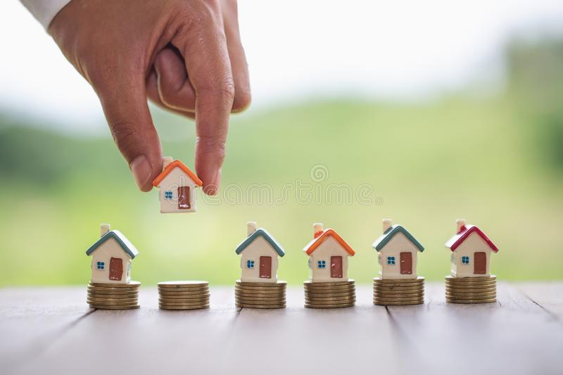Woman`s hand putting house model on coins stack. Concept for property ladder, planning savings money of coins to buy a home stock photos