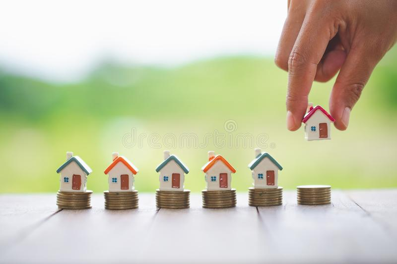 Woman`s hand putting house model on coins stack. Concept for property ladder, planning savings money of coins to buy a home stock photography