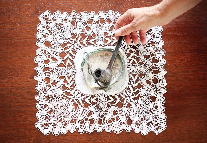 Woman´s hand putting wooden pipe on ashtray from seashell. Crocheted tablecloth. Woman´s hand putting wooden pipe on ashtray from seashell. Crocheted stock photo