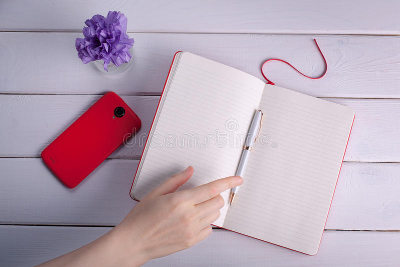 Woman`s hand reaches for a ball-point pen. The thoughts in a notebook stock photos
