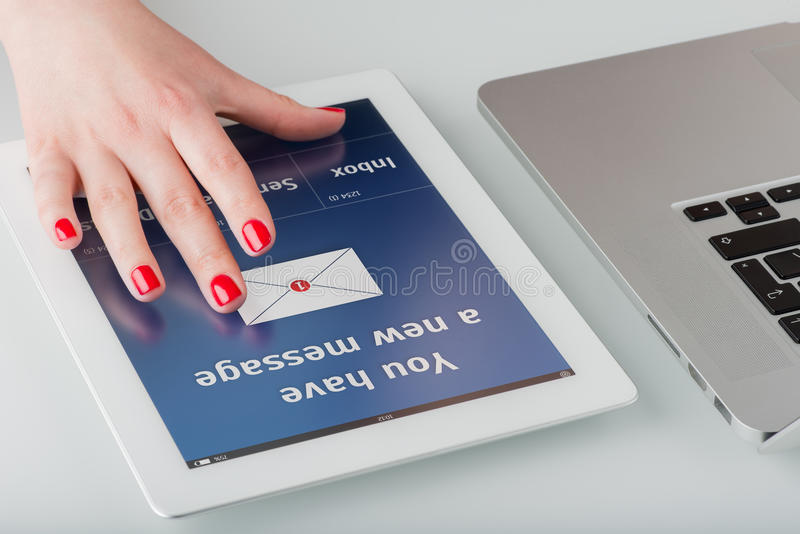 The hand on the tablet computer. Woman's hand with red manicure opens a new email message on a tablet computer stock photography