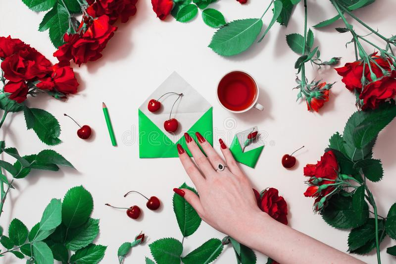 Woman`s hand with red nails with a silver ring with black stone. Corundum and rim theon. Red tea, small envelopes with green leaves roses lay on white stock photography