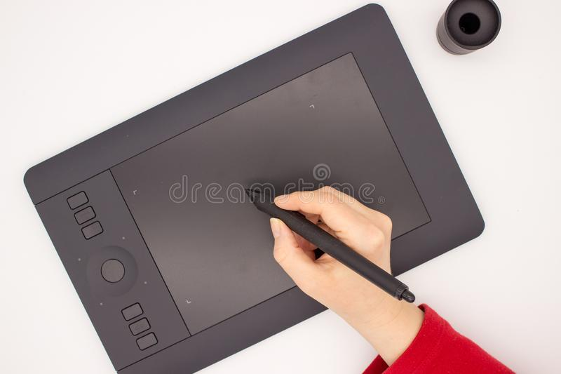 A woman`s hand in a red sleeve draws a stylus on a graphics tablet. stock image