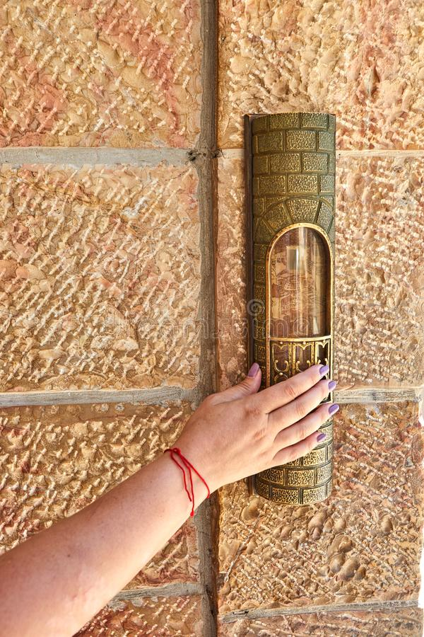 A woman& x27;s hand with a red thread touches the mezuzah at the entrance to the area near. The Western Wall, holy, cityscape, jerusalem, kotel, shrine, mosque stock photo