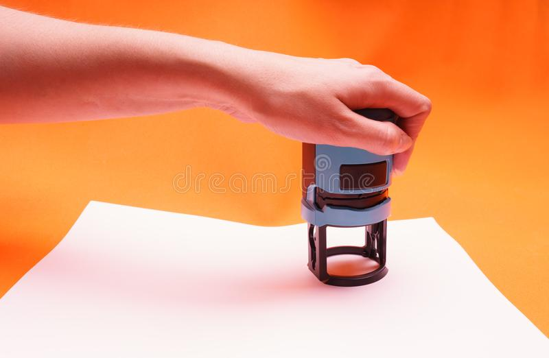 Woman`s hand with the seal, stamp. Process stamping the contract, documents, close up. royalty free illustration
