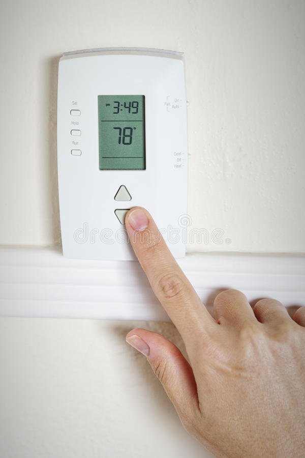 A woman's hand setting the room temperature on a modern digital programmable thermostat royalty free stock images