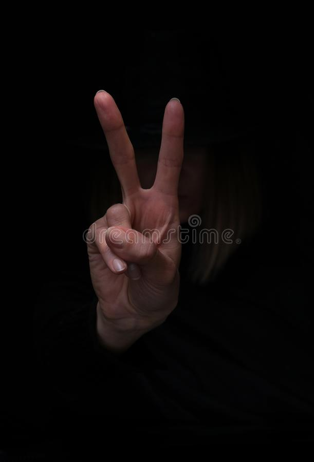 Woman`s hand showing V-sign, victory peace gesture, isolated on black background. stock photography