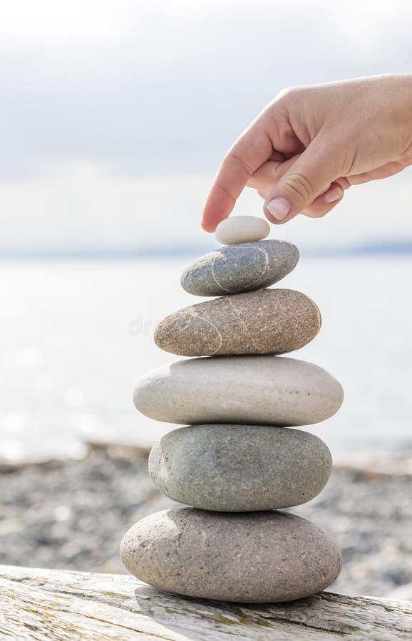 Woman& x27; s-hand som balanserar en bunt av stenar på en drivvedstrandjournal royaltyfria foton