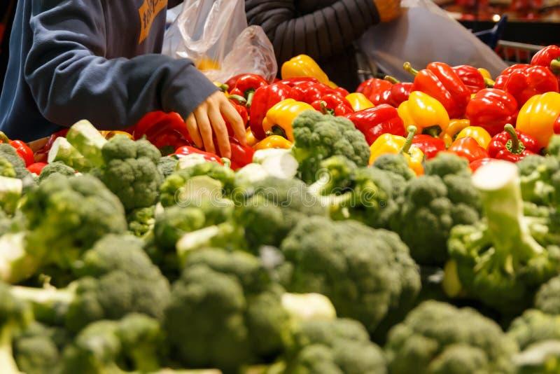woman' s-hand som upp väljer grönsaker på livsmedelsbutikmarknaden fotografering för bildbyråer