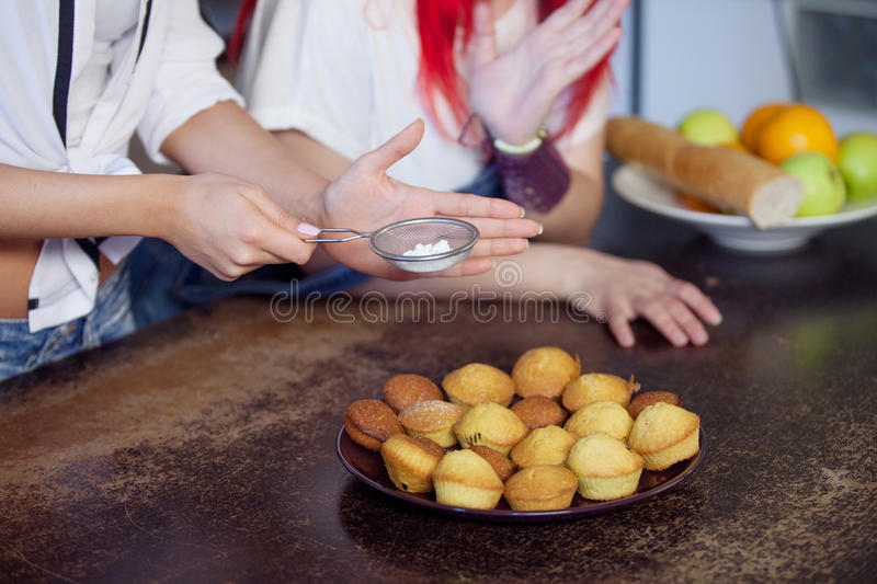Woman& x27;s hand sprinkling icing sugar over fresh muffins. close up. Woman& x27;s hand sprinkling icing sugar over fresh muffins stock image