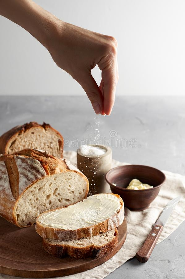 Woman`s hand sprinkling sugar artisan sliced toast bread with butter on wooden cutting board. Simple breakfast royalty free stock image