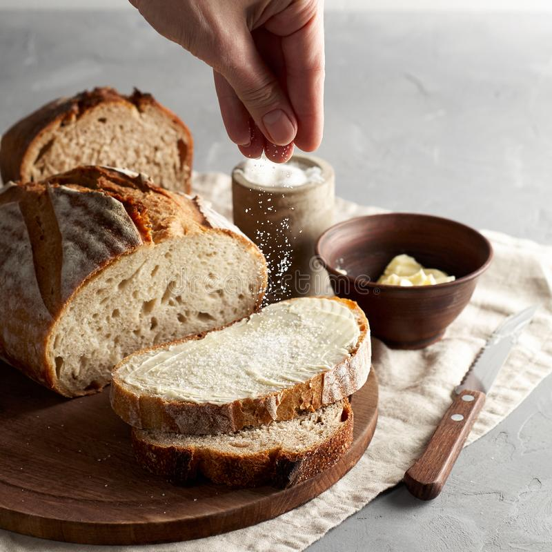 Woman`s hand sprinkling sugar artisan sliced toast bread with butter on wooden cutting board. Simple breakfast. On grey concrete background royalty free stock photography
