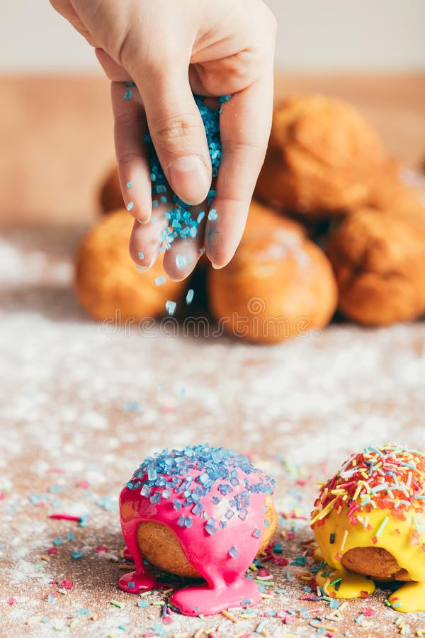 Woman sprinkling sugar strands on doughnuts. Woman`s hand sprinkling sugar strands on colorful doughnuts. Decoration stock images