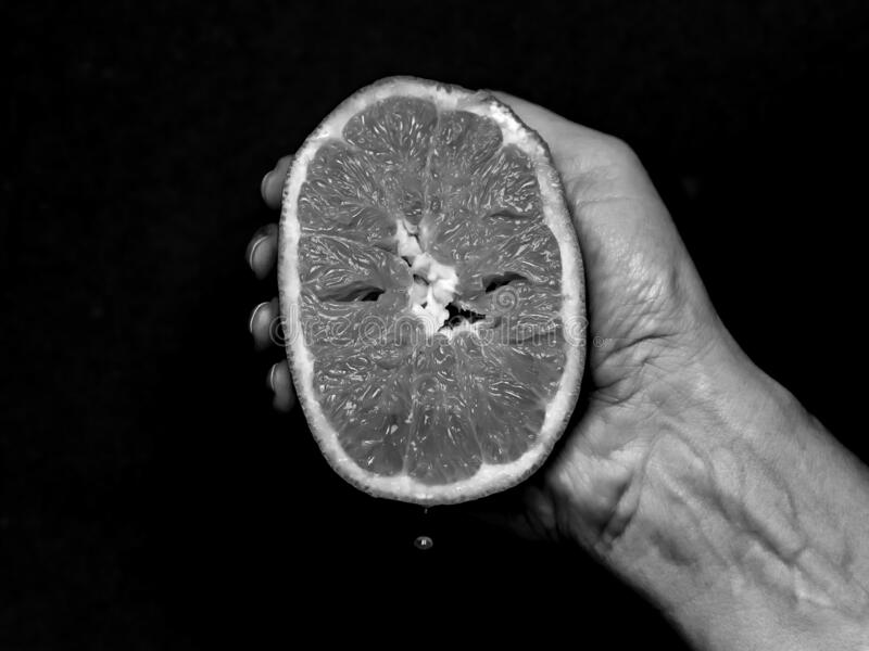 Woman`s hand squeezes half an orange until a drop of juice falls, in black and white stock image