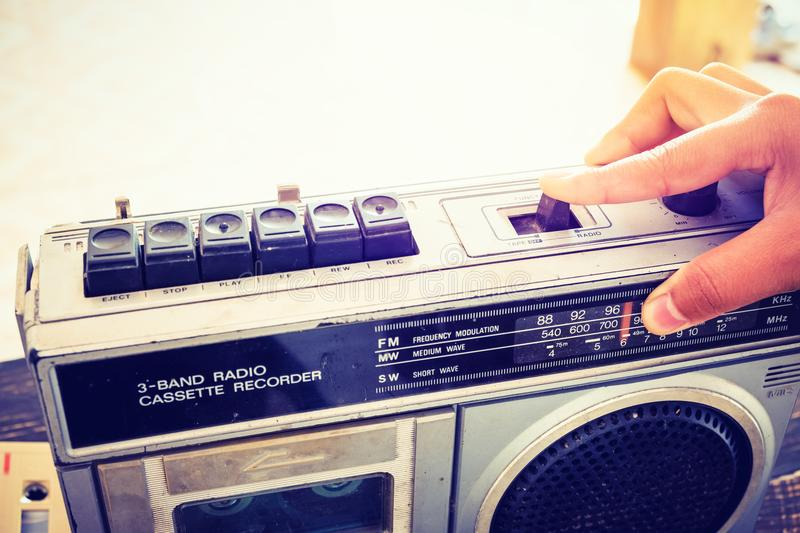 Woman`s hand switched and adjusting button cassette player. Retro lifestyle - Woman`s hand switched and adjusting button cassette player and recorder for listen royalty free stock photo