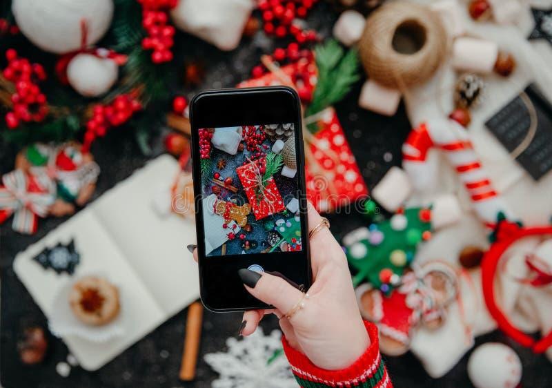 Woman`s hand take a mobile photo of christmas composition. stock image