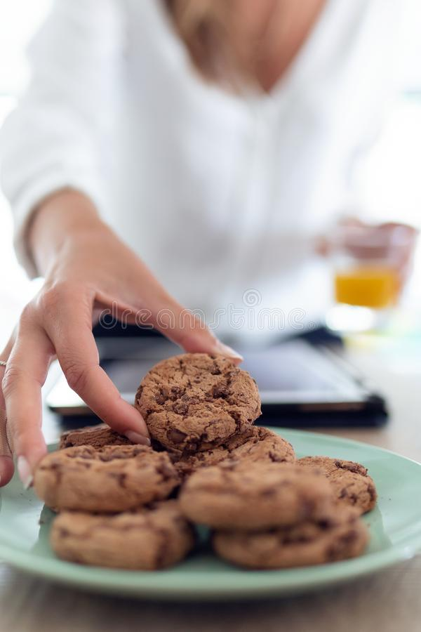A woman`s hand taking chocolate cookies from a plate while holding an orange juice in the other hand. Close-up of a woman`s hand taking chocolate cookies from a royalty free stock images