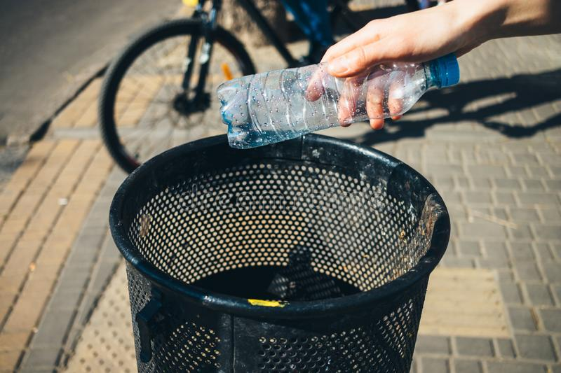 Woman's hand throws empty plastic water bottle stock photos