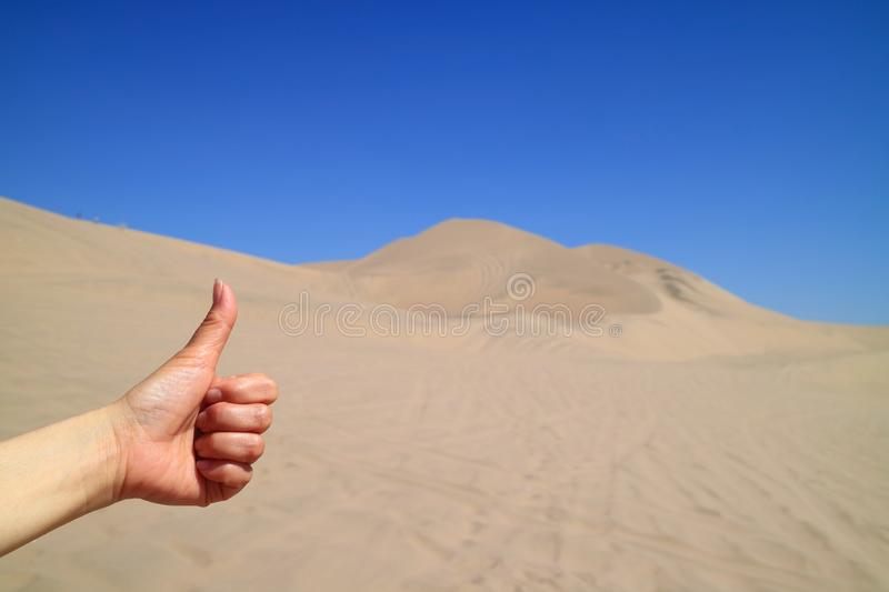 Woman`s Hand Thumbing Up to the Amazing View of Huacachina desert in Ica region of Peru. South America, adventure, blue, bright, clear, color, dry, dune royalty free stock images